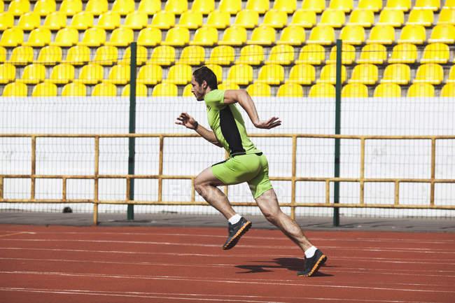 Полный вид сбоку на спортивного юношу, бегущего по ипподрому на стадионе — стоковое фото