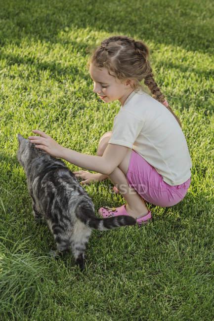 Longitud completa vista lateral de chica acariciando gato en parque - foto de stock