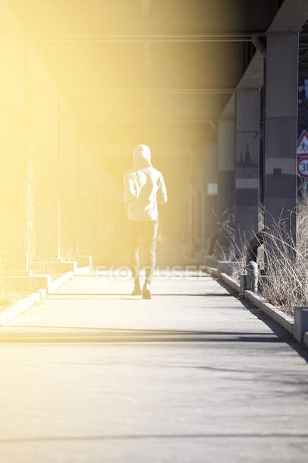 Obscured shot of man jogging on city sidewalk under bridge — Stock Photo