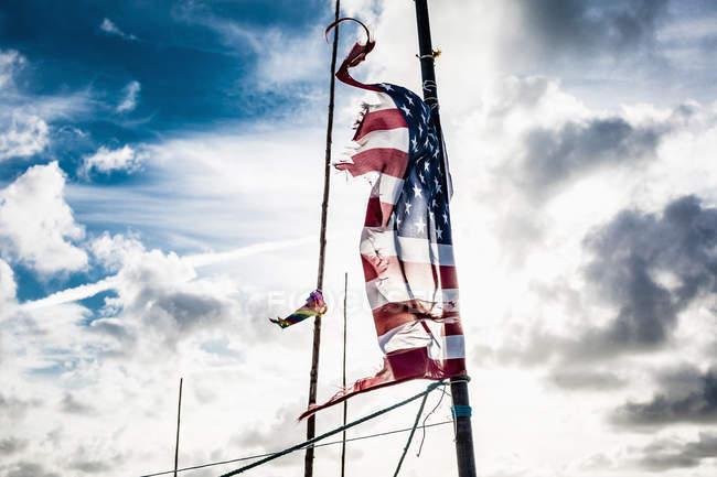 Bandiera americana stracciata su palo contro il cielo nuvoloso — Foto stock