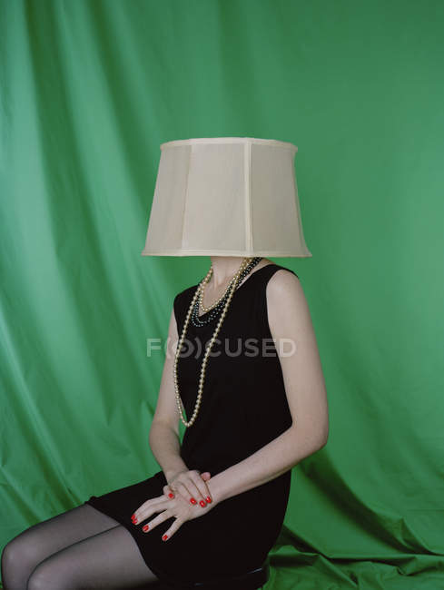 Woman in black dress wearing lamp shade on head — Stock Photo