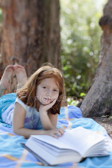 Дівчина лежав на підодіяльнику у парку з книги — стокове фото