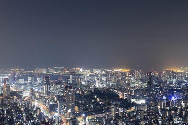Vue aérienne de cityscape lumineux dans le ciel de nuit — Photo de stock