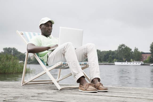 Людина розслабляючий на лежак з ноутбуком у озера — стокове фото
