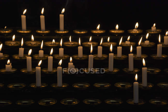 Rows of lit prayer candles on dark background — Stock Photo
