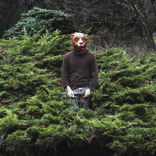 Man wearing bear mask and posing amidst plants — Stock Photo