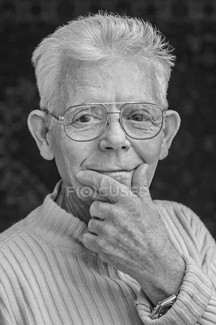 Close-up portrait of happy senior man wearing glasses over black background — Stock Photo