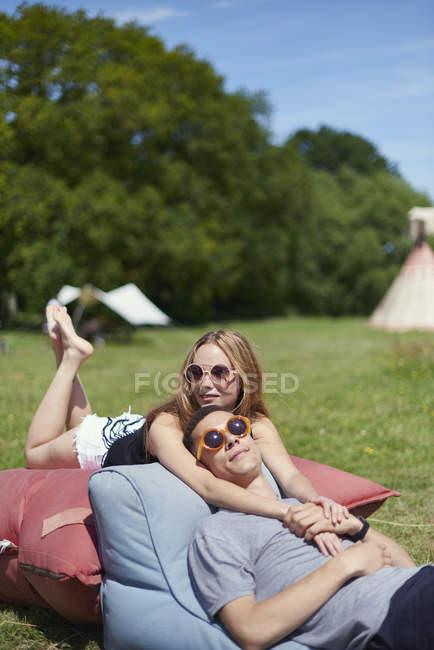 Jovem casal deitado sobre almofadas enquanto glamping — Fotografia de Stock