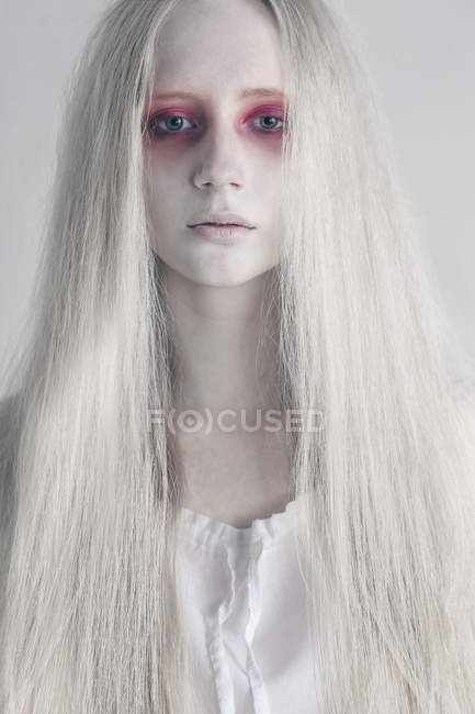 Young woman with spooky red eyes and long hair against white background — Stock Photo