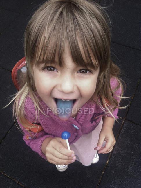 Ein kleines Mädchen hält einen blauen Sauger und zeigt stolz ihre blaue Zunge — Stockfoto