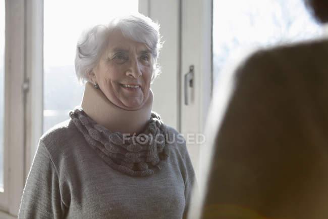 Lächelnde Seniorin mit Nackenstütze — Stockfoto
