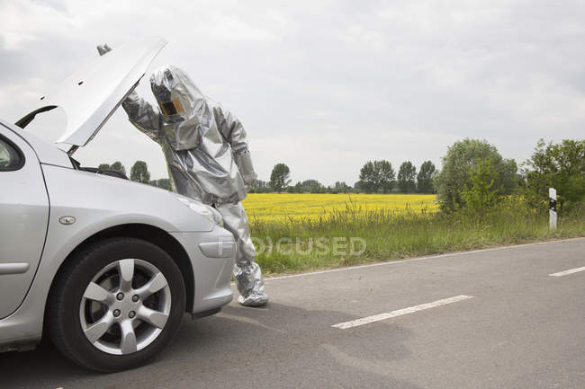 A person in a radiation protective suit looking under  hood of a car — Stock Photo