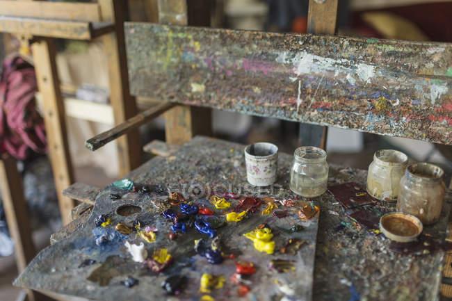 Cerrar vista de paleta y tarros con pintura en estudio - foto de stock