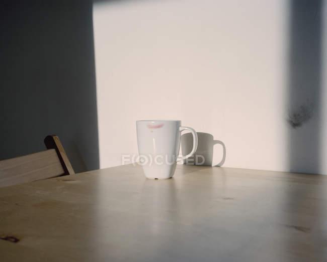 Кружка из белого кофе с помадой на столе — стоковое фото