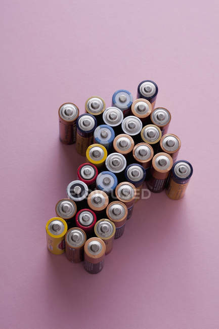 Group of batteries arranged into shape of pointing up arrow — Stock Photo