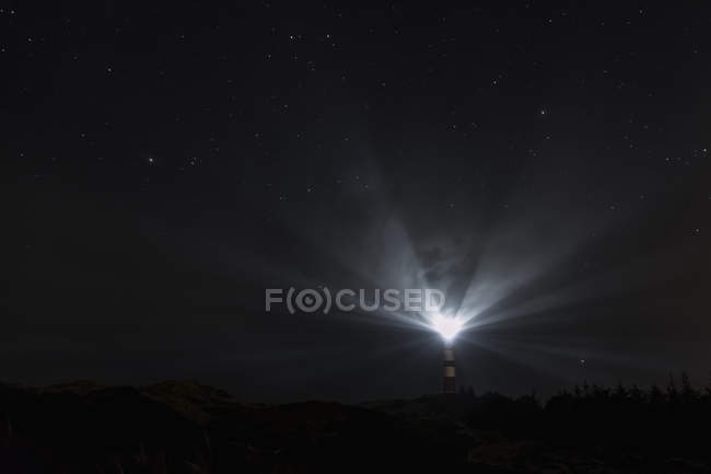 Scenic view of lighthouse signaling at night — Stock Photo