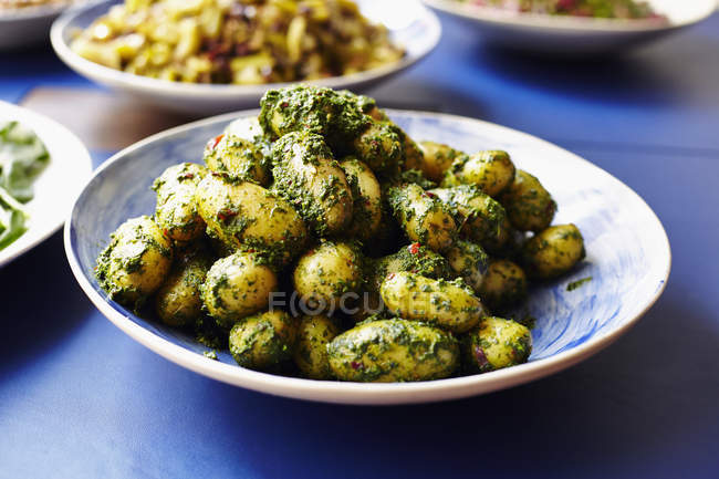 Close up of boiled potatoes served with parsley in plate at table — Stock Photo
