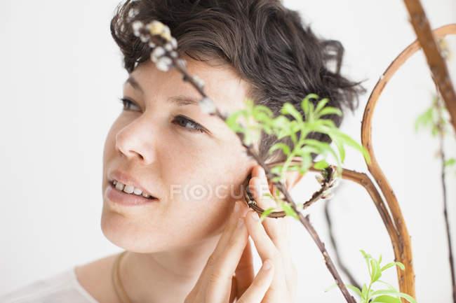 Крупный план женщины, касающейся растения на белом фоне — стоковое фото