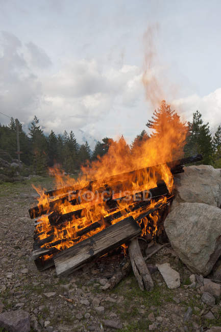 Planks of wood burning in big bonfire at nature — Stock Photo