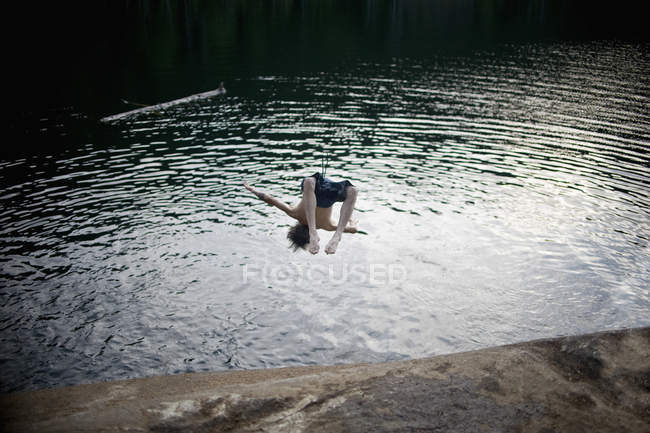 Full length of man jumping over head in lake — Stock Photo