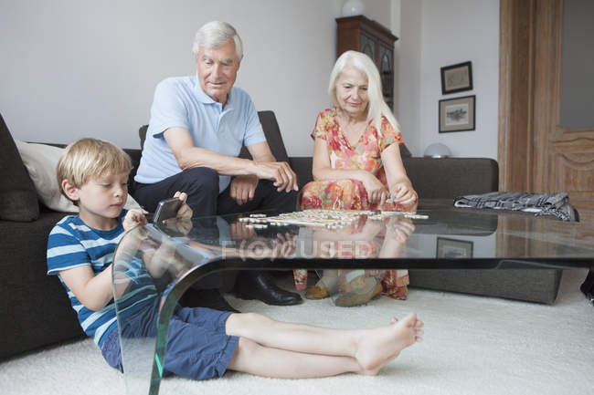 Grands-parents et petit-fils de loisirs dans le salon — Photo de stock