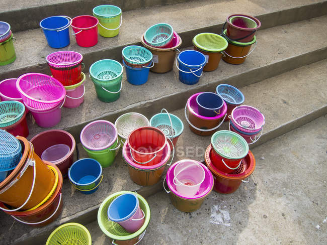 Colorful plastic baskets and buckets on steps — Stock Photo
