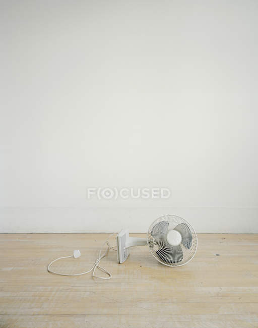Electric fan lying on its side at hardfloor — Stock Photo