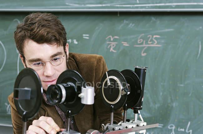 Вчитель, регулюючи науковий прилад в класі — стокове фото