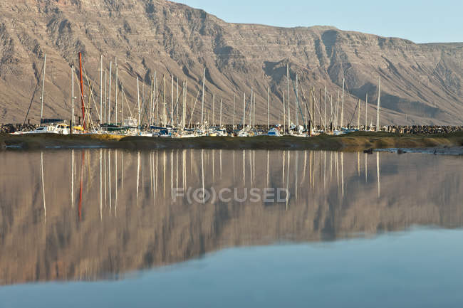 Moored yachts in calm sea by cliff side — Stock Photo