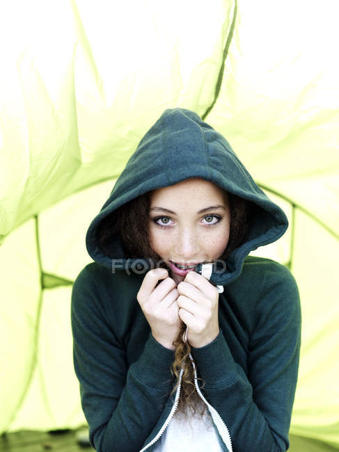 A teenage girl sitting in a tent pulling the sides of her hood sweatshirt together — Stock Photo