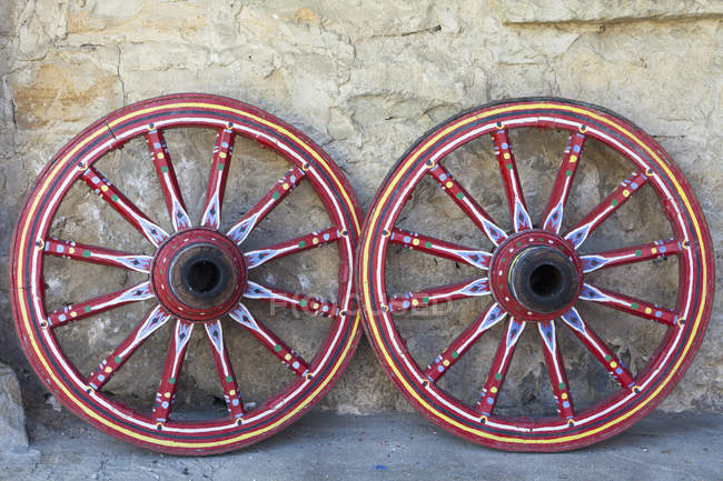 Два колеса decoratively пофарбовані вагона її до стіни — стокове фото