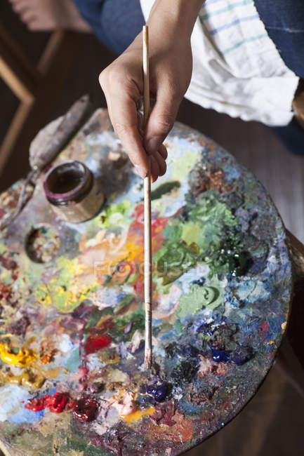 Crop artist's hand mixing paint in palette — Stock Photo