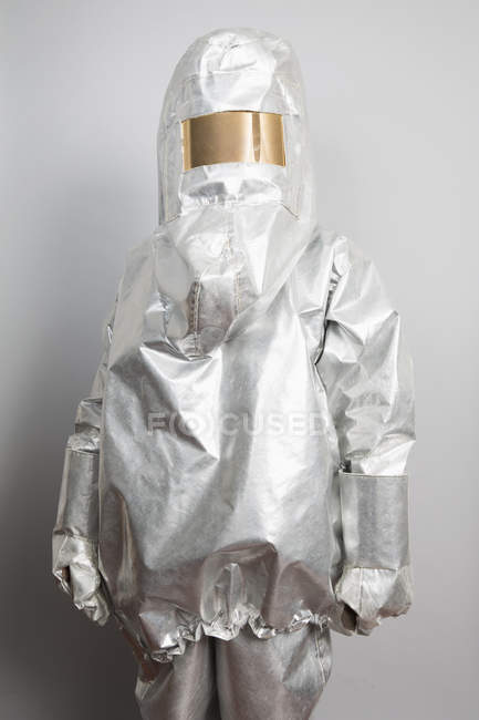 Person in radioactive protection suit standing against gray backdrop — Stock Photo