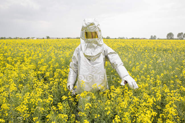 Person in radiation protective suit standing in oilseed rape field — Stock Photo