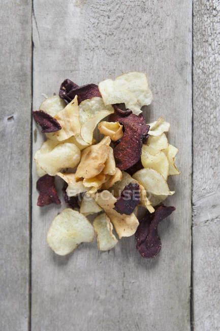 Vue directement au-dessus de la pomme de terre et de betteraves jetons sur la table en bois — Photo de stock