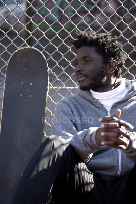 Jovem sério inclinando-se contra cerca elo cadeia ao lado do skate — Fotografia de Stock