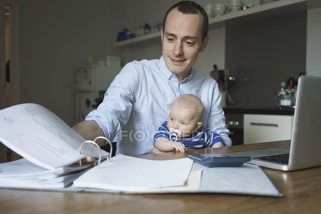 Father doing paperwork while carrying baby boy at home — Stock Photo