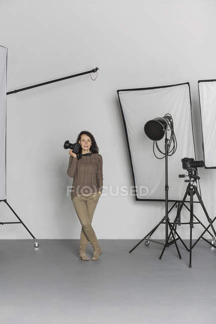Full length of mature female photographer with camera in photo studio — Stock Photo