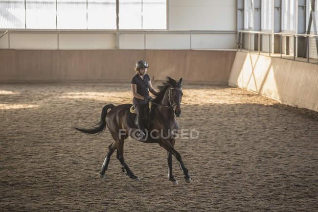Женщина верхом на лошади в тренировочной конюшне — стоковое фото