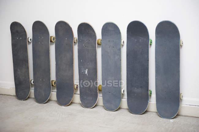 Row of skateboards arranged against wall — Stock Photo