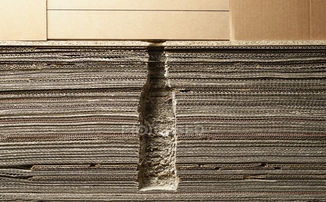 Full frame shot stacked corrugated cardboard edge with bottle silhouette — Stock Photo