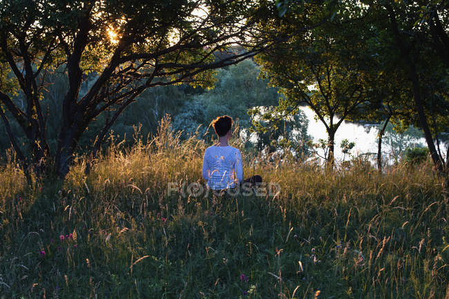 Rear view of woman meditating on grassy field by trees — Stock Photo