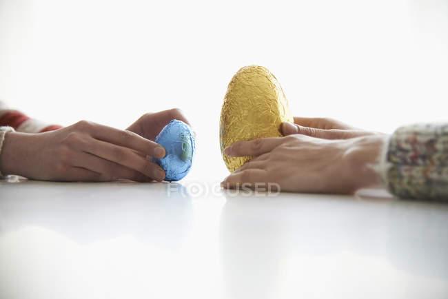 Cultivo madre e hija sosteniendo huevos de Pascua en la mesa - foto de stock