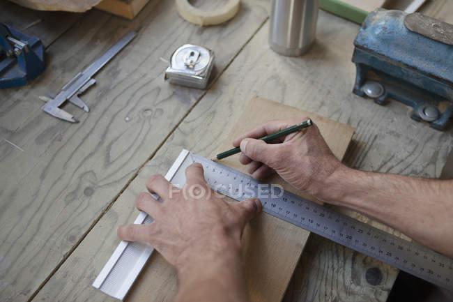 Male carpenter marking on plank in workshop — Stock Photo