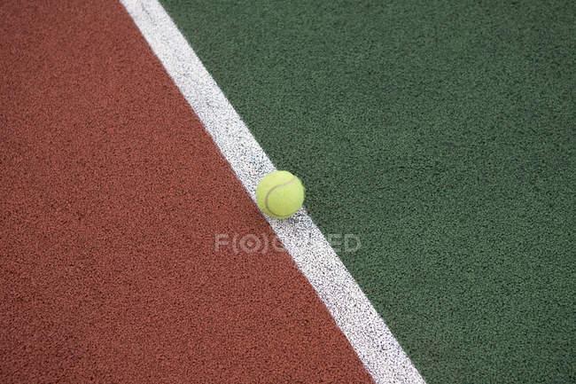 Pelota de tenis en la línea de tenis - foto de stock