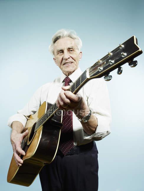 Senior Mann spielt Akustikgitarre auf blauem Hintergrund — Stockfoto