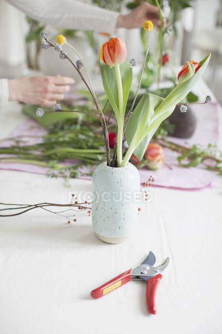 Ernte-Frau arrangieren von Blumen zu Hause auf Tisch — Stockfoto