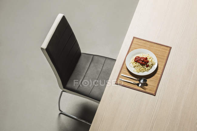 Spaghetti con sugo di pomodoro fresco serviti sul tavolo davanti alla sedia moderna — Foto stock