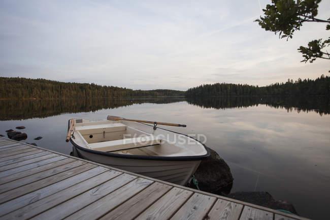 Barco atracado no cais em lago calmo — Fotografia de Stock
