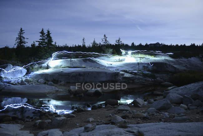 Light trails on rocky landscape at dusk — Stock Photo